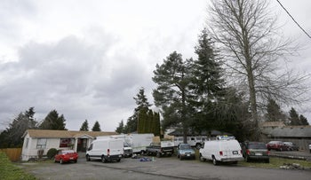 Vehicles are parked Sunday, March 5, 2017, at the home and driveway where a Sikh man was shot in the arm Friday, in Kent, Washington.