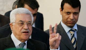 Palestinian Authority President Mahmoud Abbas, left, flashes the V-sign as then-Fatah leader Mohammed Dahlan looks on in the West Bank town of Ramallah, in 2006.