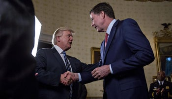 U.S. President Donald Trump shakes hands with James Comey, director of the FBI, at a reception at the White House in Washington, January 22, 2017.