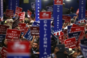 """Delegates hold signs reading """"Make America First Again"""" during the Republican National Convention (RNC) in Cleveland, Ohio, U.S., on Wednesday, July 20, 2016."""