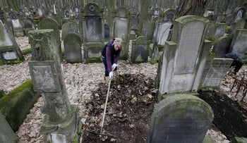 File photo: A volunteer helps to clean a Jewish cemetery in Warsaw, Poland.