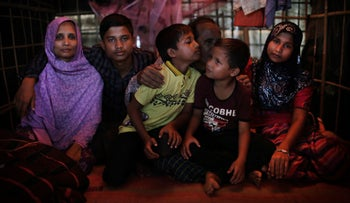 Bodru Duza, 52, third from right, kisses his sons as he sits for a portrait with members of his family in a tent in Kutupalong refugee camp in Bangladesh on November 25, 2017