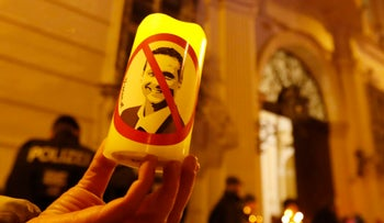 A demonstrator holds a candle with a picture of Freedom Party head Heinz-Christian Strache in a protest demanding no government participation for the far right in Vienna, Austria. November 15, 2017