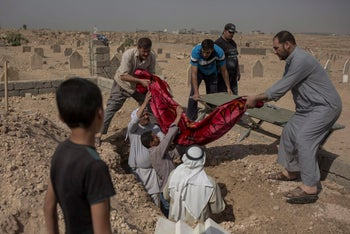 In this Oct. 9, 2017 photo, relatives bury the body of 15-year-old Sana Younes at a graveyard in Mosul