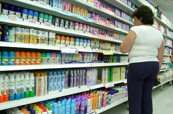Deodorant: Woman wearing white top and black trousers looks at rows of deodorant in an Israeli drugstore.
