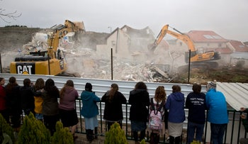 Settlers watch as bulldozers demolish houses in the West Bank settlement of Ofra, March 1, 2017.