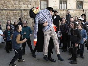 Ultra-Orthodox Jewish children wearing costumes look at a figure doll symbolising the Evil Haman from the ancient Book of Ester, during their school Purim celebration four days ahead of the official holiday on the Jewish calendar in the ultra-Orthodox Jewish neighbourhood of Mea Shearim in Jerusalem on March 8, 2017.