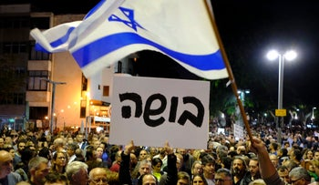 Demonstrators hold a sign reading 'shame' as they protest against corruption in Prime Minister Benjamin Netanyahu's government, Tel Aviv, Israel, December 3, 2017.
