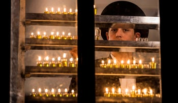 A yeshiva student lights candles on the seventh night of Hanukkah in the Ultra-Orthodox city of Bnei Brak, Israel, December 18, 2017.