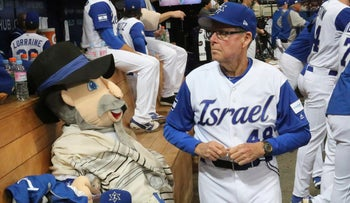 Israel's third base coach Pat Doyle, right, passes by his team mascot, The Mensch on the Bench, during at the first round game of the World Baseball Classic at Gocheok Sky Dome in Seoul, South Korea, Thursday, March 9, 2017.