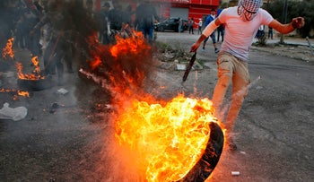 A Palestinian protester kicks a flaming tire during clashes with Israeli security forces north of Ramallah December 22, 2017.
