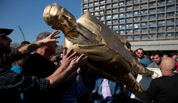 People carry a statue of Prime Minister Benjamin Netanyahu after toppling it, Tel Aviv, Israel, December 6, 2016.