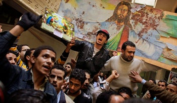 File photo: Egyptian Coptic Christians hold a blood-spattered poster depicting Jesus Christ after the morning mass inside the Saints Church in Alexandria, Egypt, Sunday, Jan. 2, 2011.