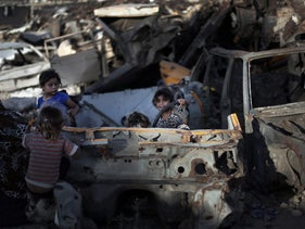 Palestinian children play among discarded vehicles in a slum near the Khan Younis refugee camp in Gaza in June 2016.