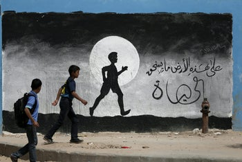 Two Palestinian schoolboys walk past a graffiti painted on a wall of the United Nations school of Beit Hanoun, in the northern Gaza Strip, on May 9, 2016.