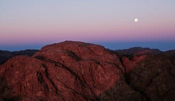 The sun rises as the moon sets from the view on top Mount Sinai or 'Mount Moses' in Saint Catherine in the Sinai peninsula, Egypt, Friday, Oct. 6, 2017.