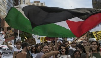 A protester waves a Palestinian flag as he demonstrates with others against the Republican National Convention (RNC) in Cleveland, Ohio, U.S., on Sunday, July 17, 2016.