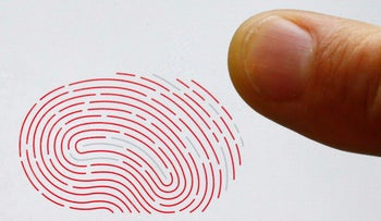 A person uses a sensor for biometric identification on a smartphone.