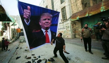 A Palestinian demonstrator throws a shoe on a poster depicting U.S. President Donald Trump during a protest in the West Bank city of Hebron February 24, 2017.