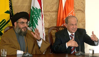 Hezbollah Secretary-General Hassan Nasrallah with Michel Aoun in 2006. Aoun, now Lebanon's president, has said Hezbollah's arms are part of his country's defense against Israel.