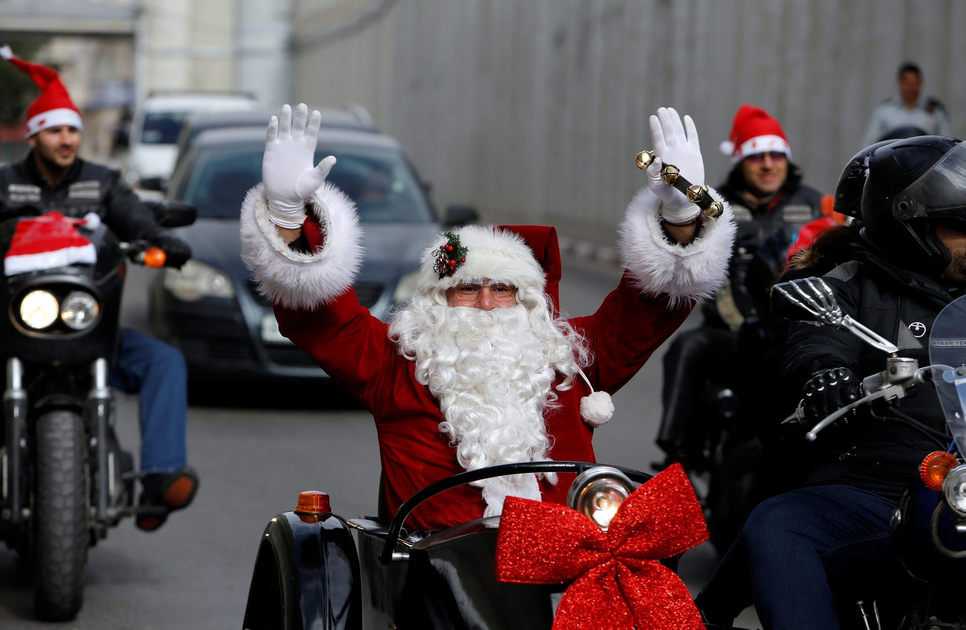 A man dressed as Santa Claus gesturing as the convoy of the Latin Patriarch of Jerusalem arrives through an Israeli checkpoint to attend Christmas celebrations in the West Bank city of Bethlehem, December 24, 2017.