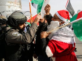 A Palestinian dressed as Santa Claus during a protest in the West Bank city of Bethlehem, Dec. 23, 2017