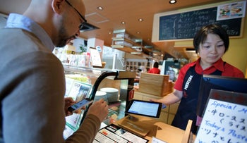 A customer uses PayPal's mobile payment application to make a purchase at a coffee shop, Tokyo, Japan, November 18, 2013.