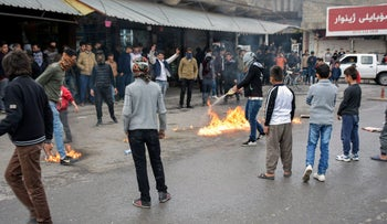 A protester pouring oil on a fire in a street during a demonstration against political corruption in the city of Rania, north of Sulaymaniyah in the autonomous Iraqi Kurdistan region, December 20, 2017.