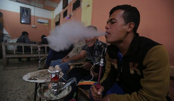 Iraqis smoke nargile at a cafe south of Mosul following its liberation by Iraqi forces, March 11, 2017.