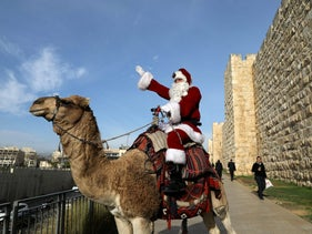 Issa Kassissieh rides a camel wearing a Santa Claus costume in Jerusalem's Old City, December 21, 2017.