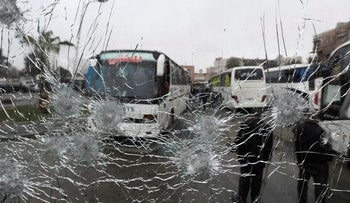 People are seen though a shattered glass window of a bus at the site of an attack by two suicide bombers in Damascus, Syria  March 11, 2017.