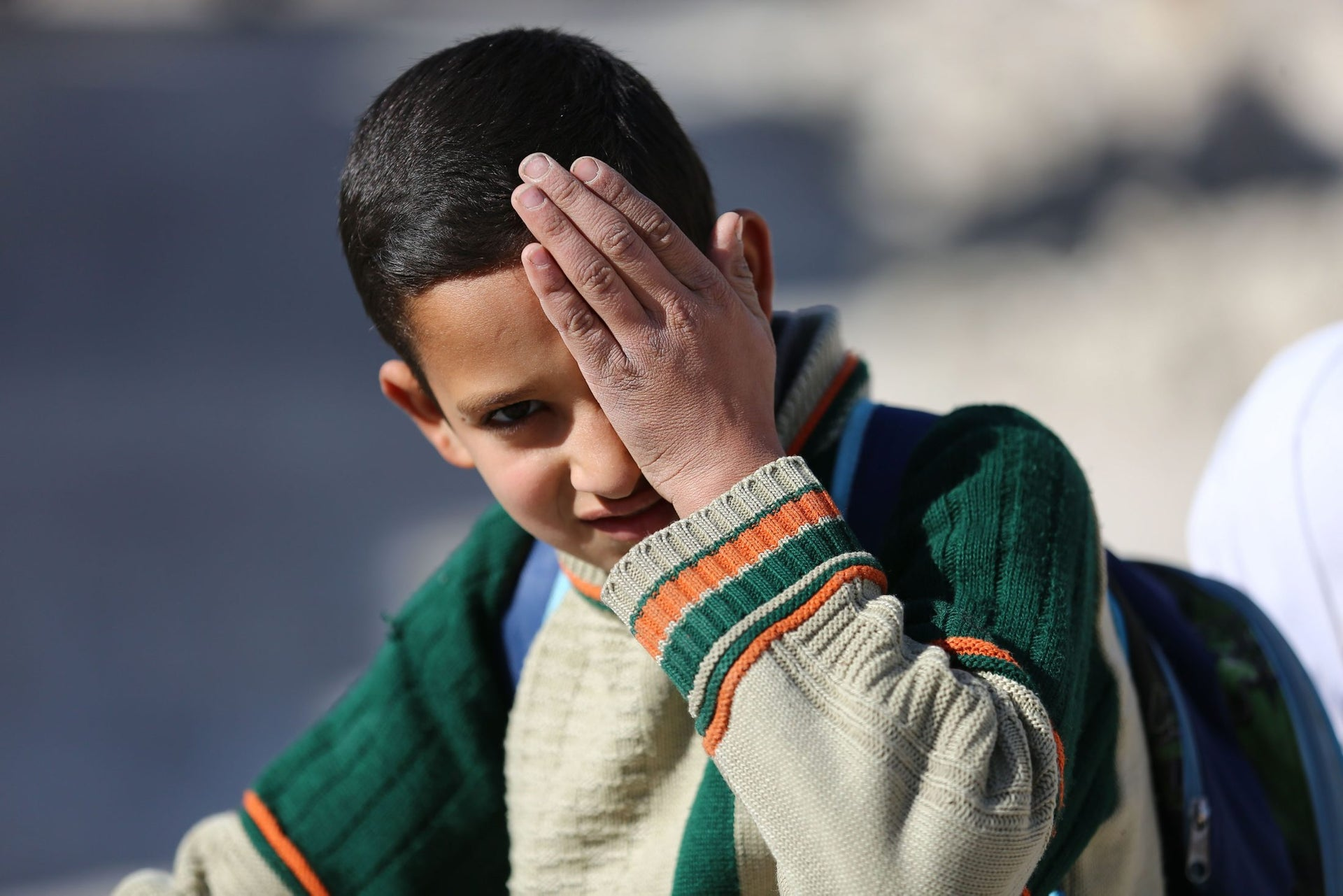 A child poses covering one eye with his hand in the rebel-held town of Douma in Syria's besieged eastern Ghouta region, on December 18, 2017, as part of a campaign in solidarity with a baby boy, Karim Abdallah, who lost an eye, as well as his mother, in government shelling on the nearby town of Hammouria.