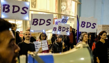 People hold signs calling for BDS at an anti-corruption protest against Prime Minister Benjamin Netanyahu in Tel Aviv, December 23, 2017.