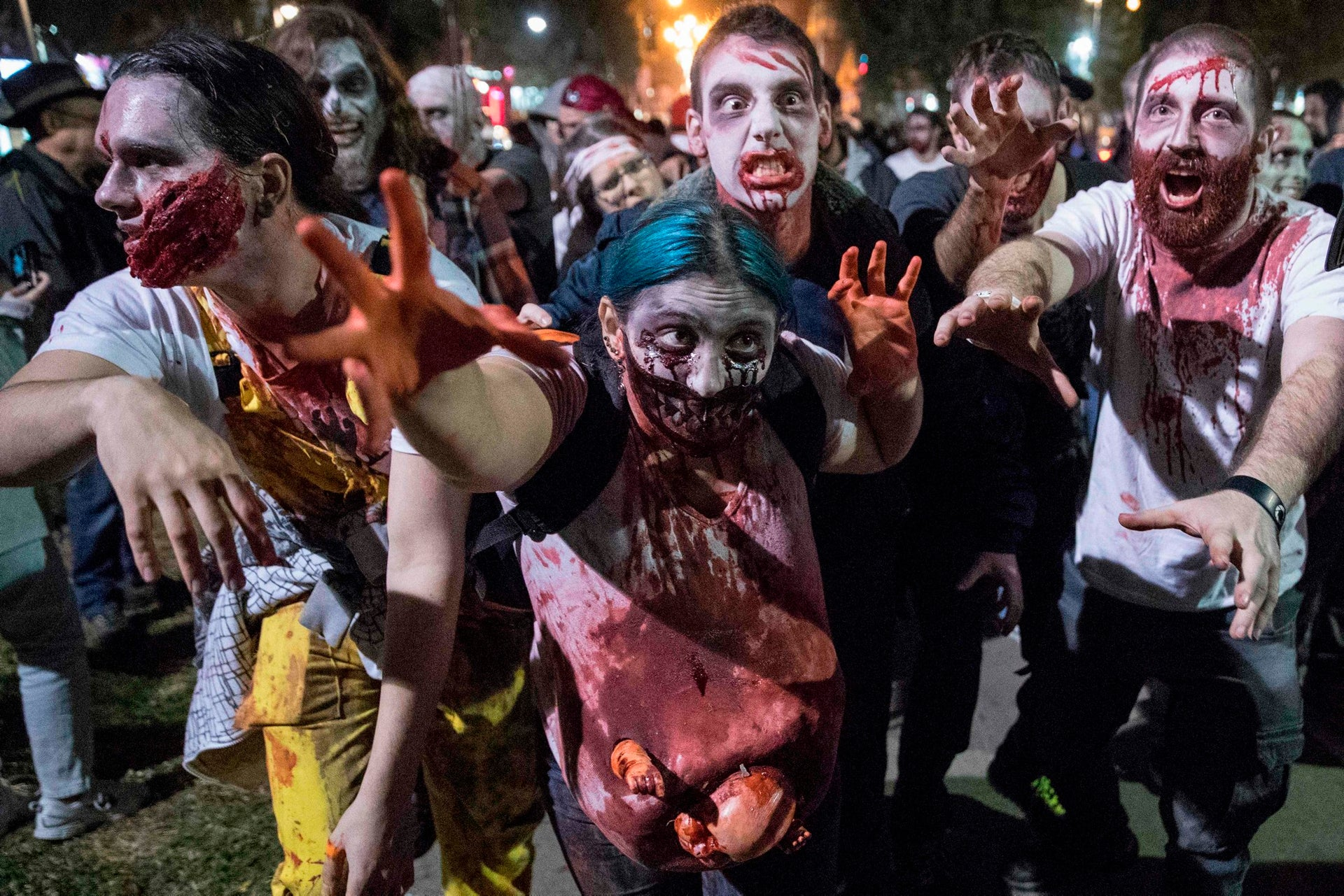 """People wearing costumes and face paint take part in a """"Zombie walk"""" in Tel Aviv as part of the Jewish holiday of Purim on March 11, 2017."""