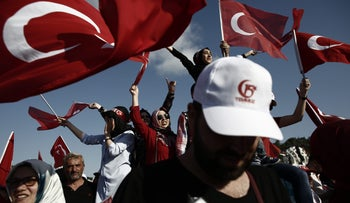 People wave Turkish flags on the anniversary of last year's failed coup, Istanbul, Turkey, July 15, 2017