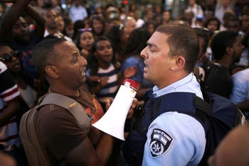 Protester clash with police officers during a protest against police brutality toward Ethiopians.