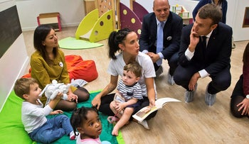 File photo: French President Emmanuel Macron speaks to children at a day care near Paris in October, 2017.