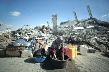 A woman washing clothes by hand in devastated Gaza, 2014.