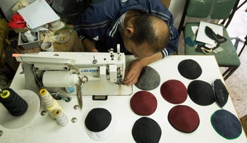 A Palestinian man works in a studio in Gaza City producing kippot, Jewish religious skullcaps