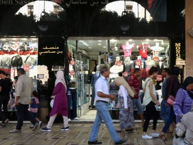 People walk past a clothes shop in Tunis, Tunisia, September 21, 2017