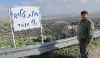 Mahmoud Abu Qubeita standing by the sign of the unauthorized ranch, with his family's land in the background.