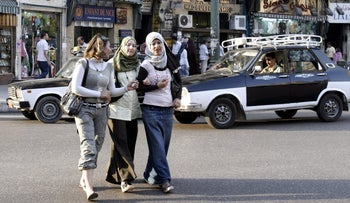 Young women cross the street arm in arm in Talaat Harb Square in downtown Cairo.