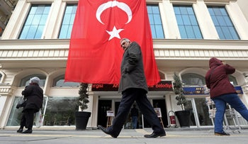 Pedestrians pass a giant Turkish national flag handing from a building in Ankara, Turkey, on December 20, 2016.