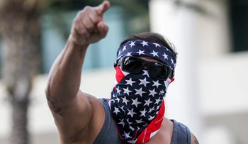 A demonstrator masked with a U.S. flag protests outside of California Republican Convention in Anaheim, Calf., on Friday, Oct. 20, 2017. Former White House adviser Steve Bannon wants to oust Republican senators he feels are disloyal to President Donald Trump. Bannon is scheduled to deliver a keynote speech at the convention, just days after leveling a blistering attack on Senate Majority Leader Mitch McConnell and other top Republicans at an Arizona fundraiser. (