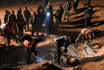 Syrian forces excavate a site, said to be a mass grave by state news agency SANA, west of Raqa province, on December 29, 2017.