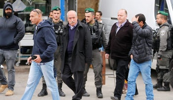 Palestinian geographer Khalil Tufakji (C) is detained as Israeli security forces carry out a police order to close his mapping office in East Jerusalem, March 14, 2017.