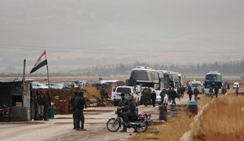 Syrian government forces stand on their checkpoint as buses wait to evacuate Syrian militants and their families from Beit Jin village, Syria, Dec. 29, 2017.