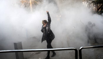 An Iranian woman raises her fist amid the smoke of tear gas at the University of Tehran during a protest driven by anger over economic problems, in the capital Tehran on December 30, 2017.