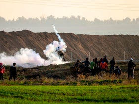 Palestinian protesters clash with Israeli soldiers near the border fence east of Gaza City on December 29, 2017.