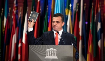 UNESCO ambassador Carmel Shama-Hacohen displays a Bible as he addresses the 39th session of the General Conference at UNESCO headquarters in Paris, November 3, 2017.